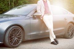 Jong, gelukkig, bedrijfsmens in de auto Mens in kostuums die zich door duur, sportwagen bevinden Succesvolle jonge mens stock foto