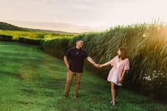 Jong gelukkig bezet paar die buiten bij zonsondergang lopen royalty-vrije stock afbeeldingen