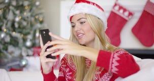 Jong gelukkig blond meisje in Kerstmisuitrusting die mobiele telefoon met behulp van stock videobeelden