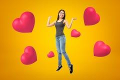 Jong gelukkig donkerbruin meisje die toevallige jeans en t-shirt met roze harten op gele achtergrond dragen stock foto's