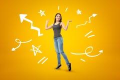 Jong gelukkig donkerbruin meisje toevallige jeans en t-shirt met beeldverhaalpijlen dragen, lijnen en sterren die op gele achterg royalty-vrije stock fotografie