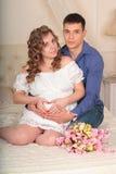 Jong gelukkig elegant zwanger paar die in slaapkamer in camera kijken Stock Afbeeldingen
