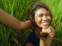 Jong gelukkig en exotisch eilandbewoner Aziatisch meisje van Indonesië die selfie zelfportretfoto met het mobiele telefoon vroli stock foto's