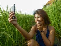 Jong gelukkig en exotisch eilandbewoner Aziatisch meisje van Indonesië die selfie zelfportretfoto met het mobiele telefoon vroli stock foto