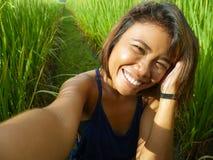 Jong gelukkig en exotisch eilandbewoner Aziatisch meisje van Indonesië die selfie zelfportretfoto met het mobiele telefoon vroli royalty-vrije stock afbeelding