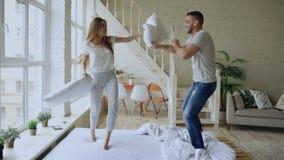 Jong gelukkig en houdend van paar die hoofdkussenstrijd in bed hebben thuis royalty-vrije stock foto's