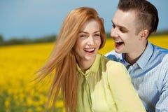 Jong gelukkig en paar die koesteren lachen Stock Foto's