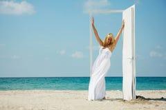 Jong gelukkig meisje dat deur op overzeese achtergrond ingaat Royalty-vrije Stock Foto's