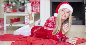 Jong gelukkig meisje die op rode deken naast open haard liggen stock video