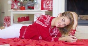 Jong gelukkig meisje die op rode deken naast open haard liggen stock footage