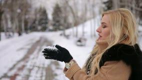 Jong gelukkig meisje die op sneeuw in het Park blazen stock video