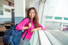Jong gelukkig meisje die op vertrek in internationale luchthaven wachten royalty-vrije stock foto