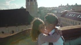 Jong gelukkig mooi modieus paar die zacht op het dak bij zonsondergang koesteren stock videobeelden