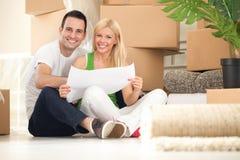 Jong gelukkig paar dat zich in hun nieuw huis beweegt stock afbeeldingen