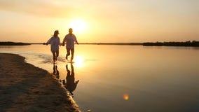 Jong gelukkig paar die aan het overzees bij zonsondergang lopen stock footage