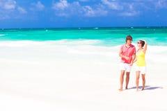 Jong gelukkig paar die bij strand het glimlachen lopen. stock foto's