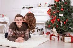 Jong gelukkig paar die dichtbij de Kerstboom het vieren omhelzen stock afbeelding