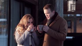 Jong gelukkig paar die een hete drank op de portiek in de winter drinken stock footage