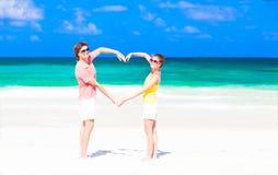 Jong gelukkig paar die hartvorm op tropisch maken royalty-vrije stock fotografie