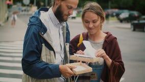 Jong gelukkig paar die in het stadscentrum samen lopen De man huidig, de vrouw die de doos openen en nemen de kaart houden stock video