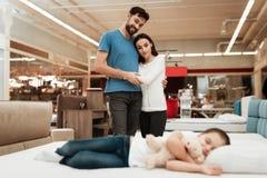 Jong gelukkig paar die op achtergrond slaap van meisje genieten Het kiezen van matras in opslag stock fotografie
