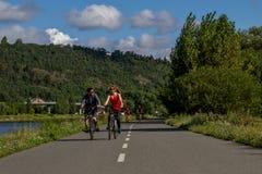 Jong gelukkig paar die op de fietsen dichtbij de rivier, op de zomerdag berijden Gezonde Levensstijl Stock Foto's