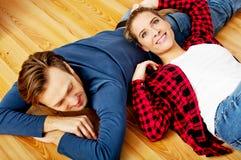Jong gelukkig paar die op de vloer liggen Stock Afbeeldingen
