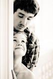 Jong gelukkig paar die rond de hoek elkaar bekijken Stock Afbeelding