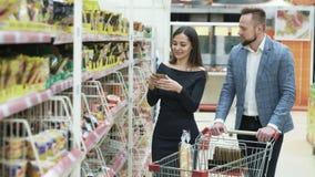 Jong gelukkig paar die in supermarkt winkelen stock footage