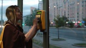 Jong gelukkig paar die zich met doos in openbaar vervoer, in tram bevinden De vrouw voor vervoer met kaartje, man wacht stock video