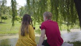 Jong gelukkig paar in liefde die picknick met wijn in mooie bloeiende tuin of en park maken die cheerfully babbelen glimlachen stock videobeelden