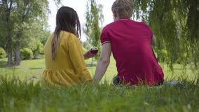 Jong gelukkig paar in liefde die picknick met wijn in mooie bloeiende tuin of en park maken die cheerfully babbelen glimlachen stock footage