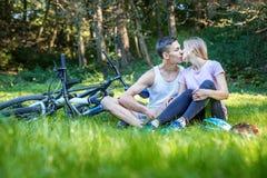 Jong gelukkig paar in liefde het kussen Het lopen in het park op bicyc Royalty-vrije Stock Foto's
