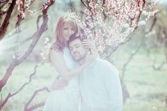 Jong gelukkig paar in liefde in openlucht houdende van man en vrouw op een gang bij de lente bloeiend park Stock Afbeelding