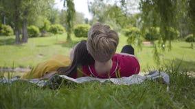 Jong gelukkig paar in liefde picknick maakt die samen liggend in mooi bloeiend en tuin of park die ontspannen glimlachen stock footage