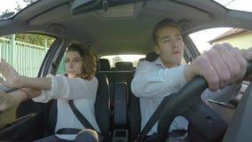 Jong gelukkig pretpaar die en in de auto zingen dansen - stock videobeelden