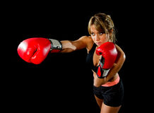 Jong geschikt en sterk aantrekkelijk boksermeisje die met rode bokshandschoenen werpend agressieve stempel opleidingstraining in  Stock Foto