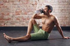 Jong geschikt mensen drinkwater het uitoefenen in een gymnastiek op oude rode bakstenenachtergrond royalty-vrije stock foto's