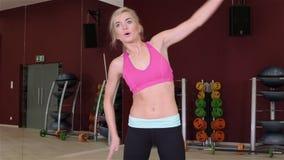 Jong geschiktheidsmeisje die in de gymnastiek uitoefenen Vrouw die uitrekkende oefeningen voor haar wapen en terug bij de gymnast stock videobeelden