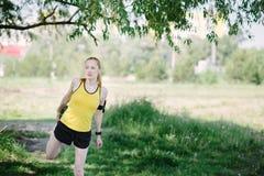 Jong geschiktheidsvrouw het uitrekken zich lichaam vóór looppas Stock Fotografie