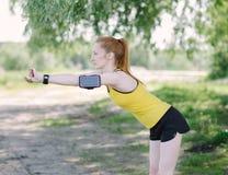 Jong geschiktheidsvrouw het uitrekken zich lichaam vóór looppas Stock Afbeeldingen