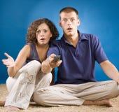 Jong geschokt paar op tapijt met afstandsbediening Royalty-vrije Stock Afbeelding
