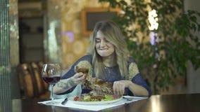 Jong getatoeeerd mooi blondemeisje die in het buitensporige tearing vlees van het dinerrestaurant met vingers ongepast gedrag ete stock video