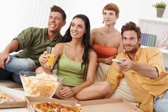 Jong gezelschap dat op TV samen let Royalty-vrije Stock Afbeeldingen