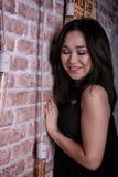Jong glamour Aziatisch meisje met gesloten die ogen aan de bakstenen muur worden geleund Stock Foto