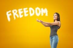 Jong glimlachend donkerbruin meisje toevallige jeans en t-shirt met palmen dragen omhoog en wit VRIJHEIDSteken die op gele achter royalty-vrije stock fotografie