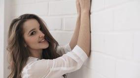 Jong glimlachend meisje die lege t-shirt dragen Baksteen witte muur op de achtergrond stock videobeelden
