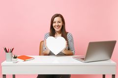 Jong glimlachend meisje die wit hart met exemplaar het ruimte werken aan project houden terwijl het zitten op kantoor met geïsole royalty-vrije stock foto