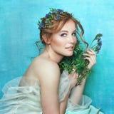 Jong glimlachend meisje met blauwe bloemen op lichtblauwe achtergrond Het Portret van de de lenteschoonheid Royalty-vrije Stock Fotografie