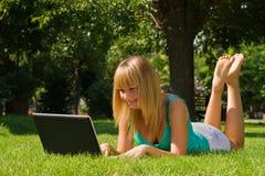 Jong glimlachend meisje op het gras met laptop Stock Foto's